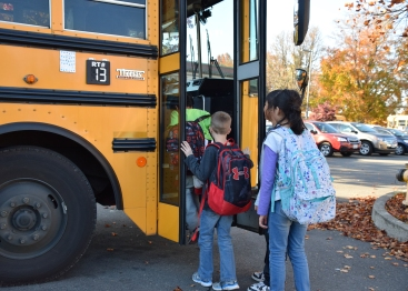 Elementary students board school bus at the end of the day