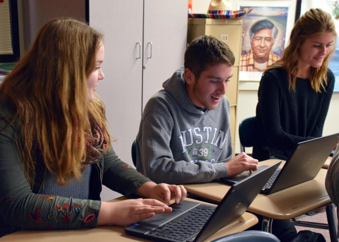 Three high school students work on laptop computers