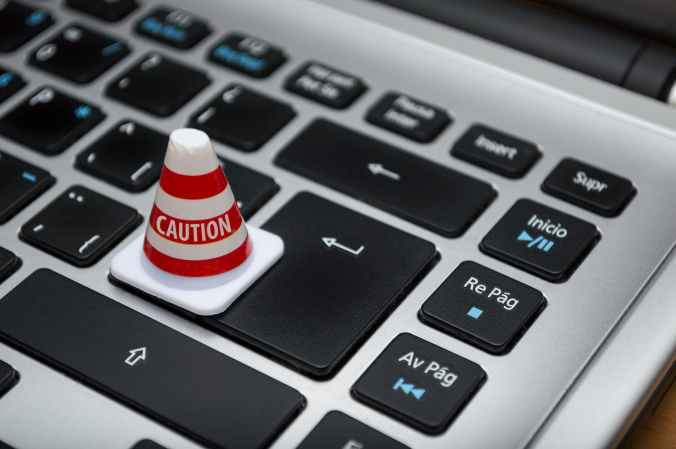 "Keyboard close-up with red and white ""Caution"" cone resting on the keyboard"