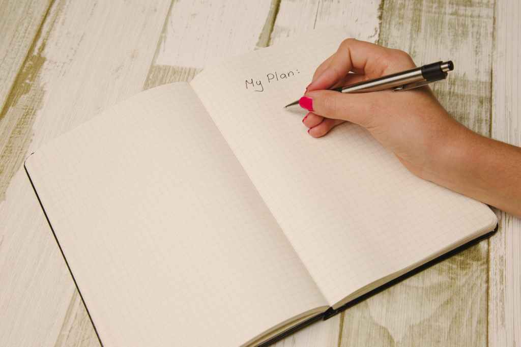 """Open notebook with words """"My Plan"""" at the top and person preparing to write with a pen"""