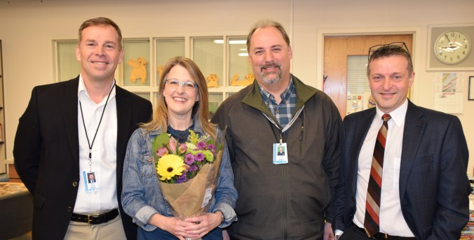 OSD Elementary Teacher of the Year Lisa Escourt is honored with flowers and poses with Superintendent Patrick Murphy, Board President Frank Wilson and Madison Principal Domenico Spatola-Knoll