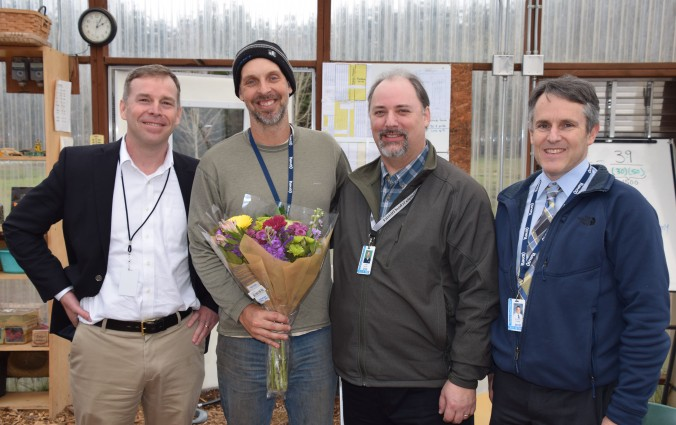 Secondary Teacher of the Year Blue Peetz holds flowers during his surprise recognition and is joined by Superintendent Patrick Murphy, Board President Frank Wilson, and Olympia High Principal Matt Grant