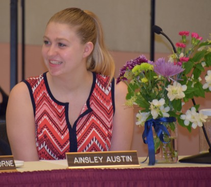 Student board representative Ainsley Austin smiles after being presented with flowers at the final school board meeting of her tenure as student rep.