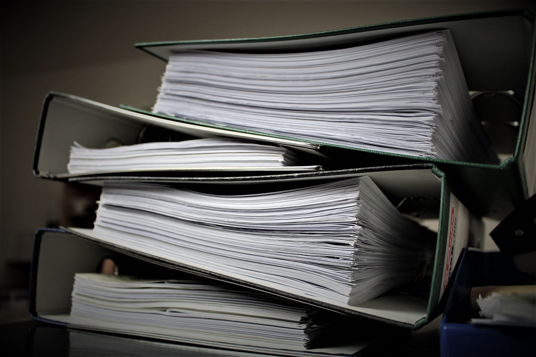 Four binders filled with papers and stacked on a desk