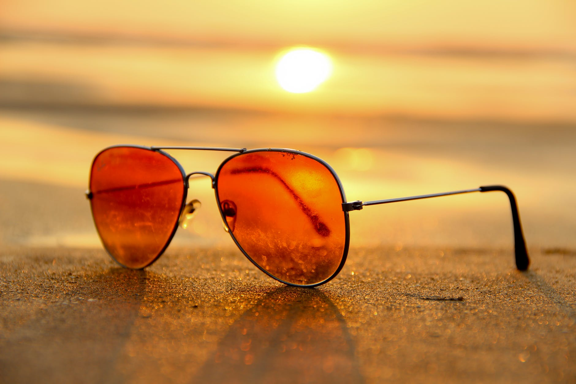 Sunglasses resting on sand with setting sun