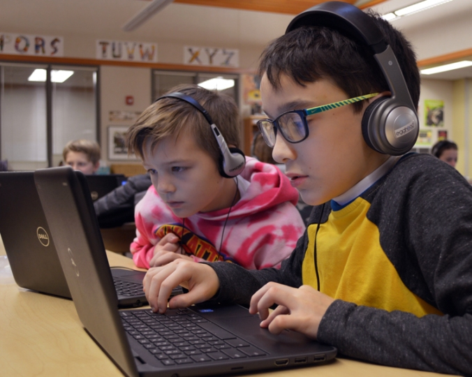 Two students work on chromebook computers while wearing headphones in a classroom setting