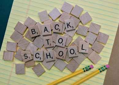 Scrabble game pieces spell out Back to School on a piece of lined paper as a welcome message to the start of the new school year