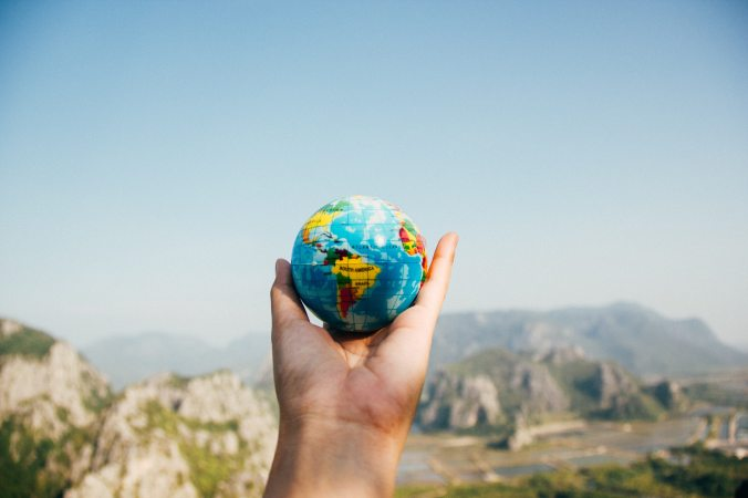 Hand holds up a world globe to represent opportunity for students to travel to a different country