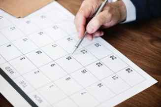 Pen points at calendar to show importance of keeping a date, in this case deadline for Open Enrollment is Sept. 28