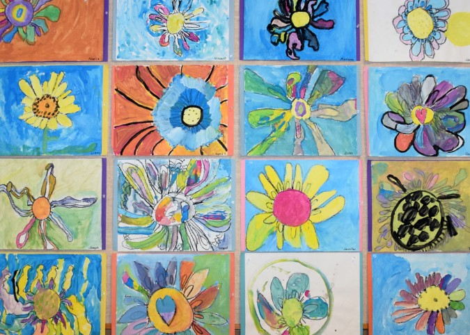 Colorful artwork of flowers created by students in the elementary visual arts program, which is expanding this year