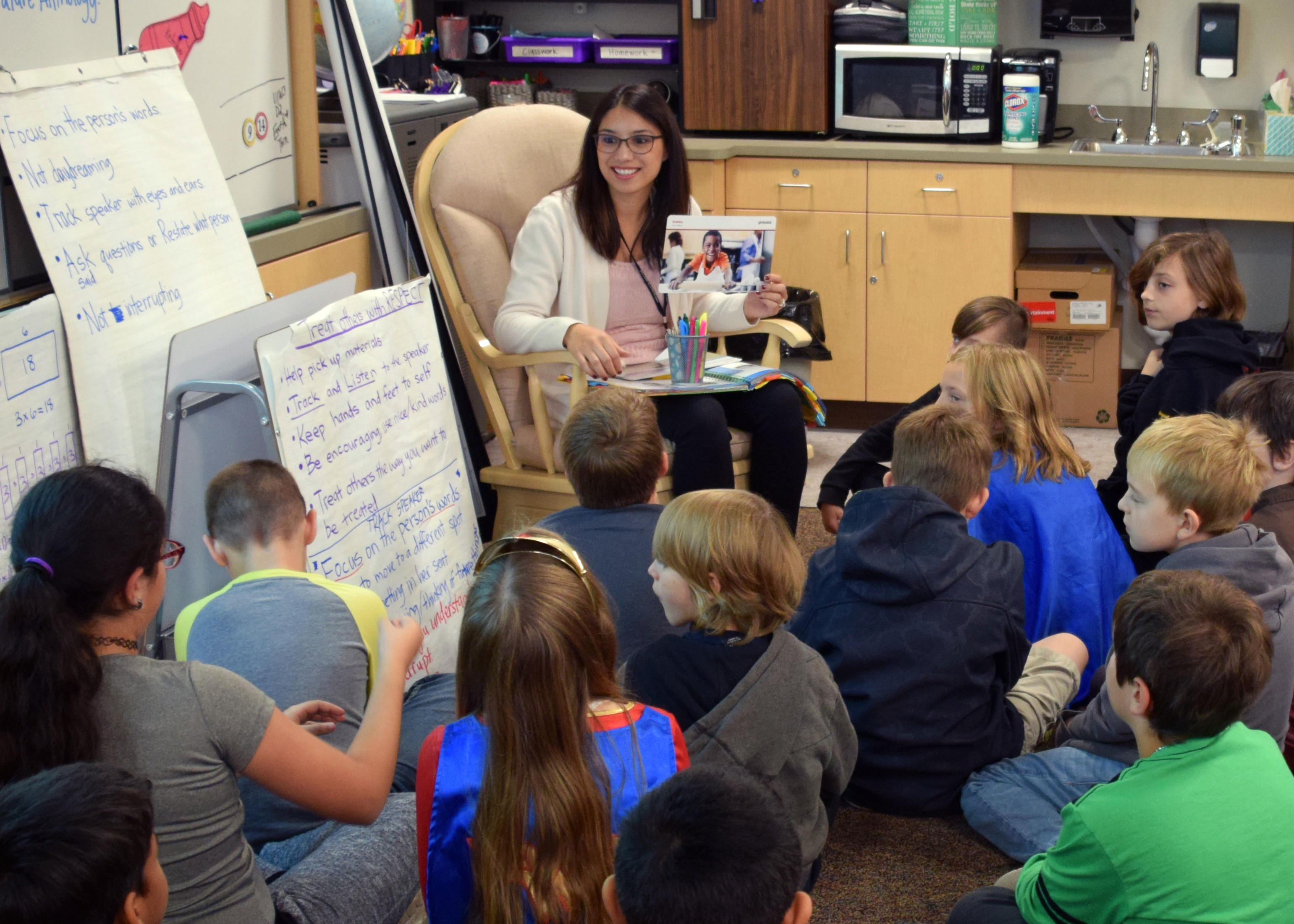 Teacher sitting in a small group circle with students shares lesson information