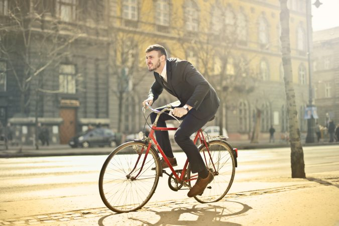 Person riding bike in suit along city street