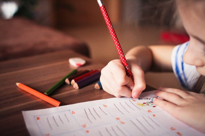 Young child writing on a piece of paper on a desk