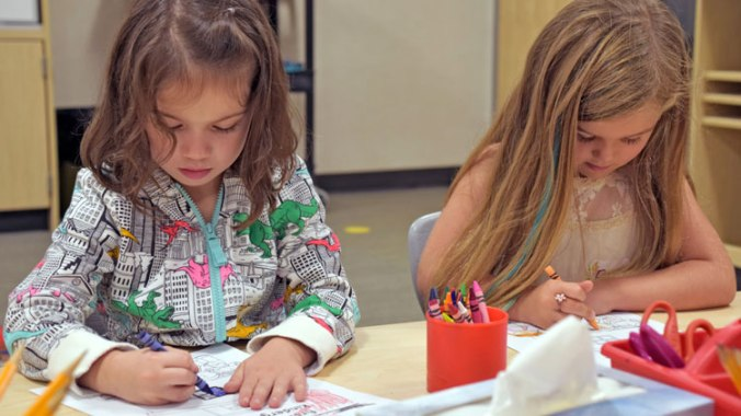 Two elementary students coloring picture in class