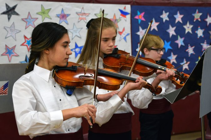 Three students play violins