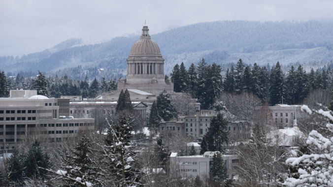 Olympia Capitol building with snow-covered hillside and trees