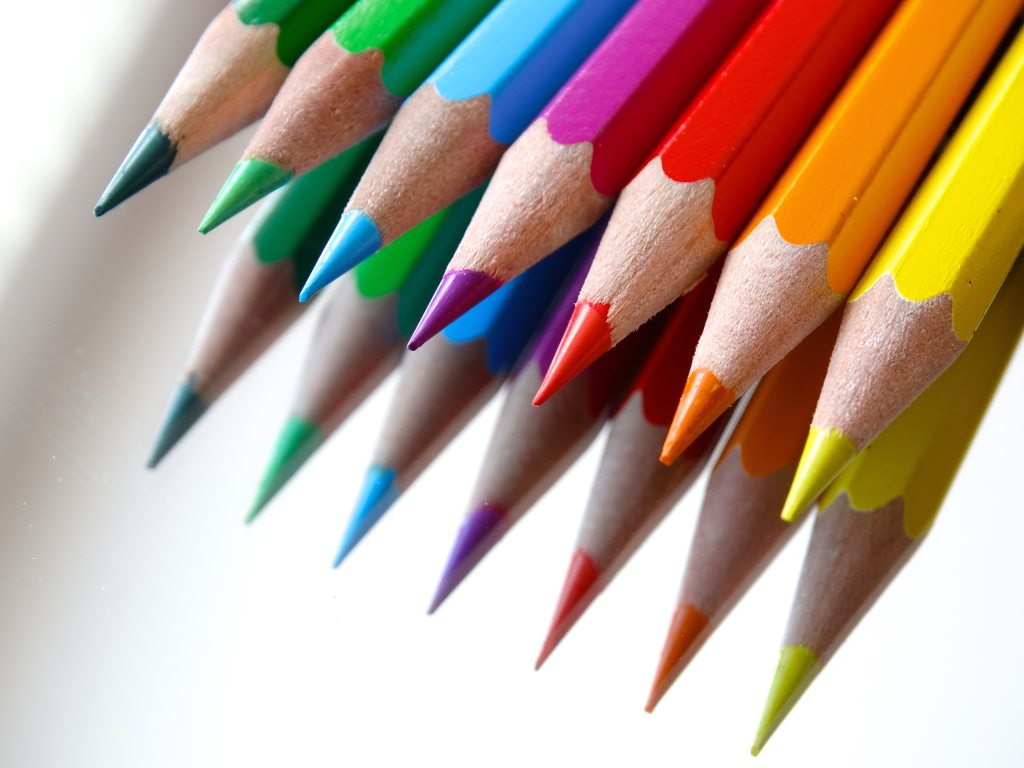 Line of sharp colored pencils with reflection
