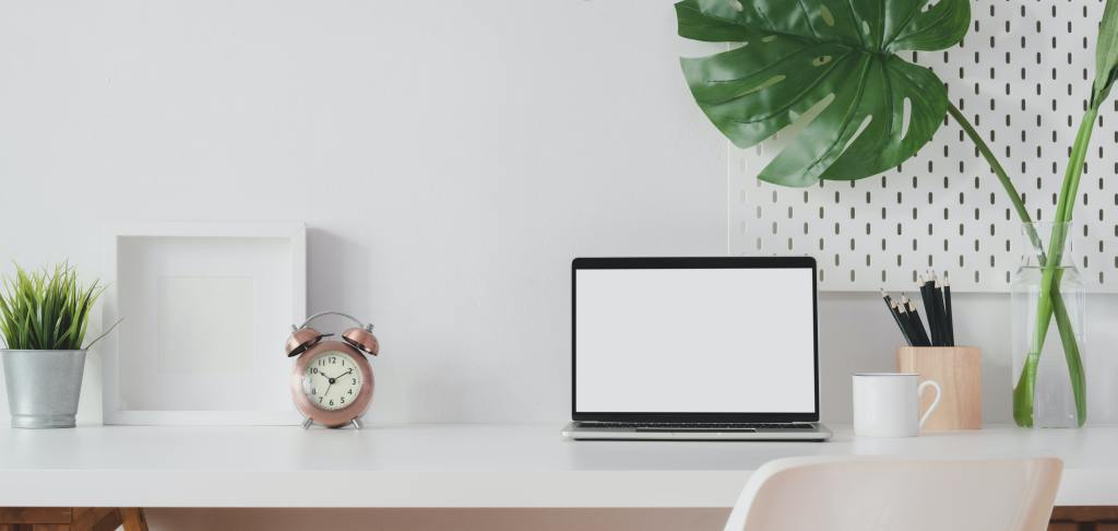 Laptop and alarm clock on a white table