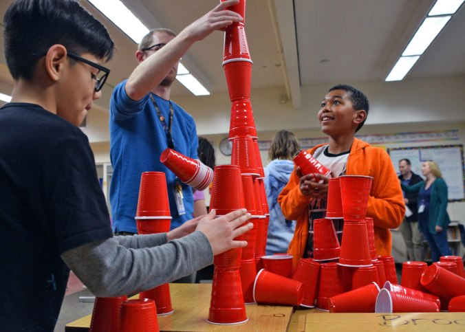 Students stack red plastic cups in tower with help from teacher