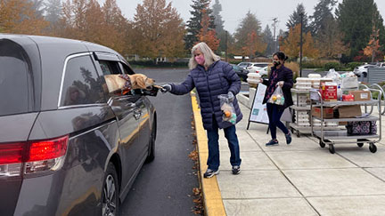 Child Nutrition Services worker brings grab-and-go meal to a waiting car in a school parking lot as part of the meal distribution program. Worker also gives a treat to a dog in the front seat of the car.