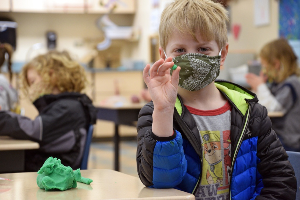 Kindergarten student holds up a ball of clay to the camera during first day of hybrid learning