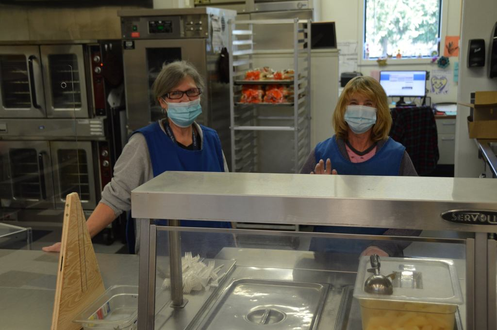 Two OSD lunch staff pose in the kitchen food prep and serving area