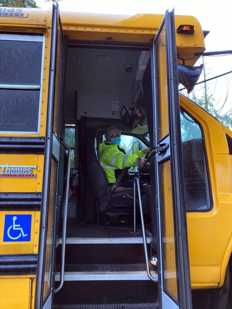 Bus driver looks at camera while seated in driver's seat with front doors open at a school stop