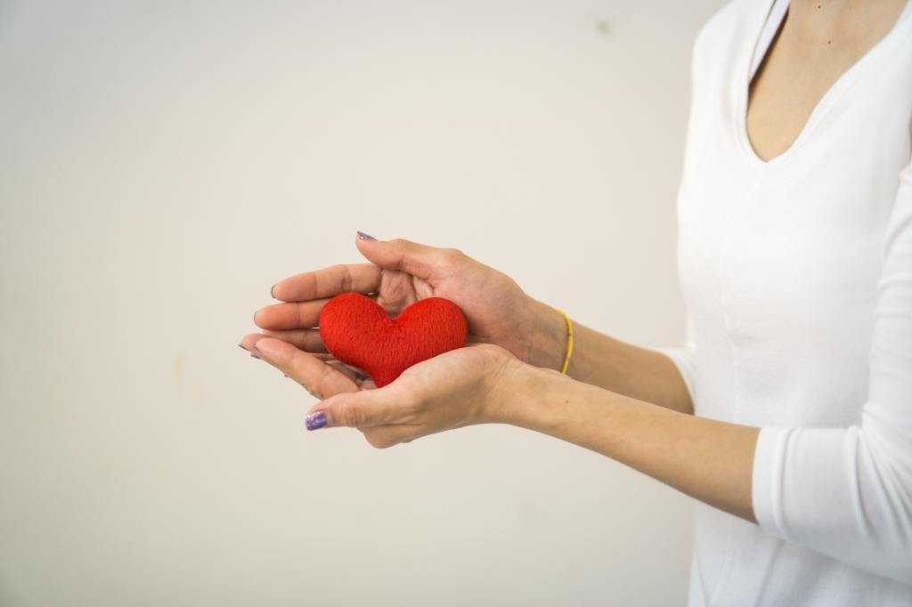 Woman holds a small fabric puffy red heart in her hands