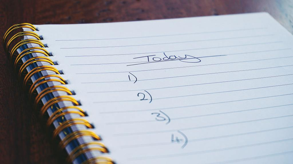"Spiral notebook lined page with the Word ""Today"" followed by a list of 1-4, symbolizing a to-do list"
