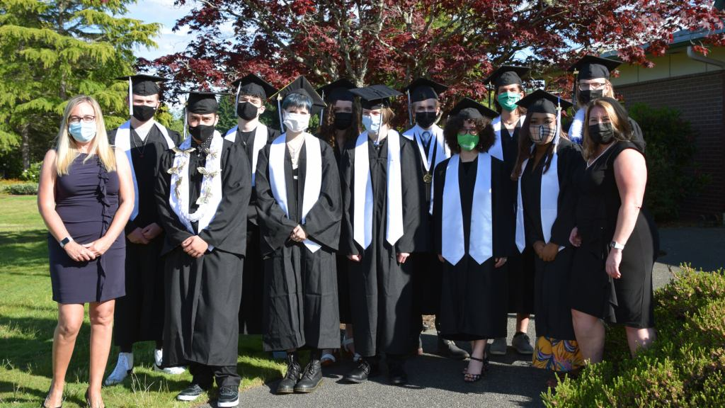 Photo of ORLA 2021 Graduates with Principal Celeste Waltermeyer and Asst Principal Kristy Grinnell outdoors  with graduates dressed in caps and gowns