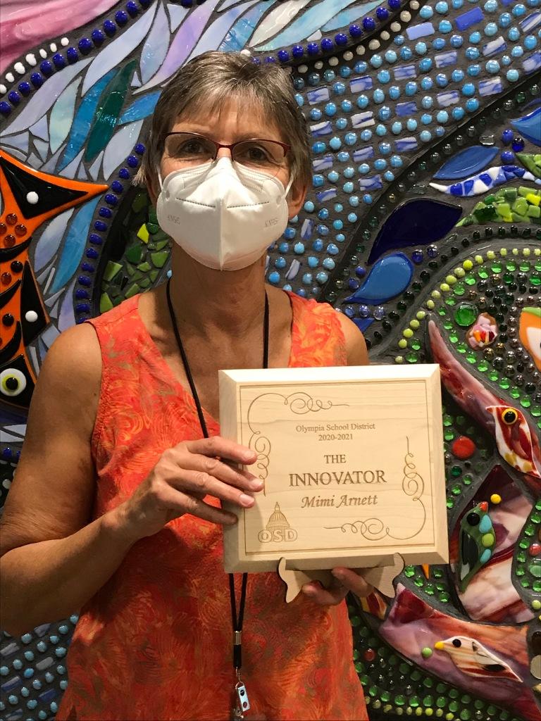 Mimi Arnett holds up plaque for The Innovator