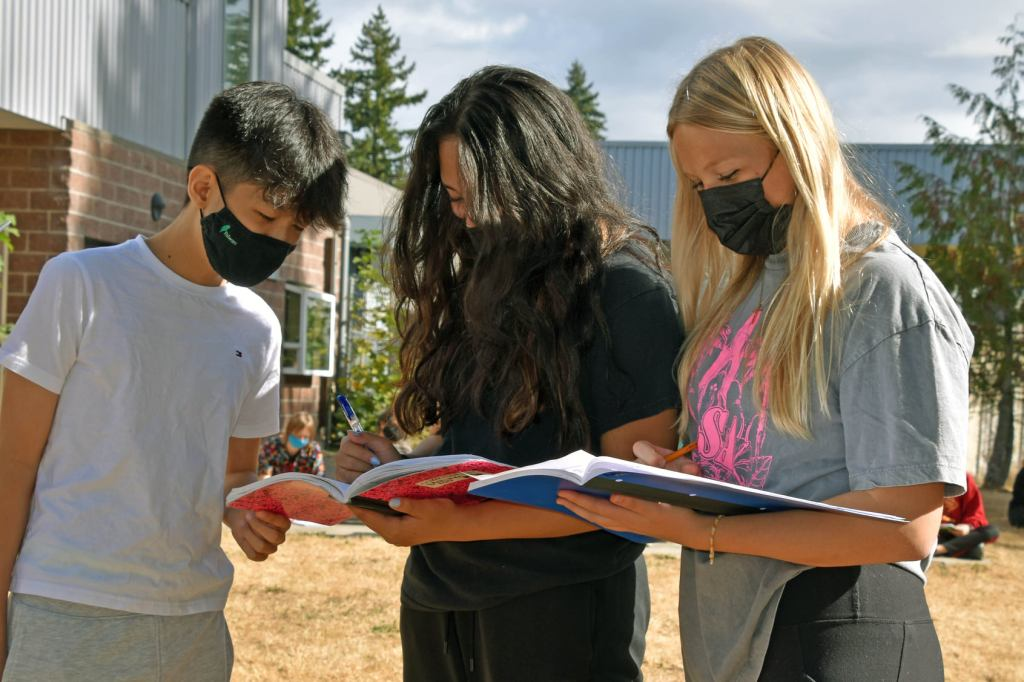 Three high school students look at notebooks while standing outdoors on campus