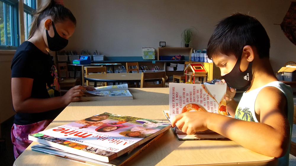 Two elementary students seated in a classroom read books at a table.