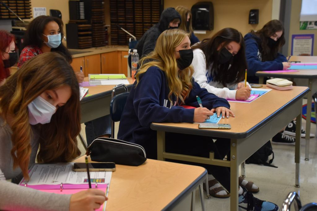 High School students write an assignment at their desks in a classroom
