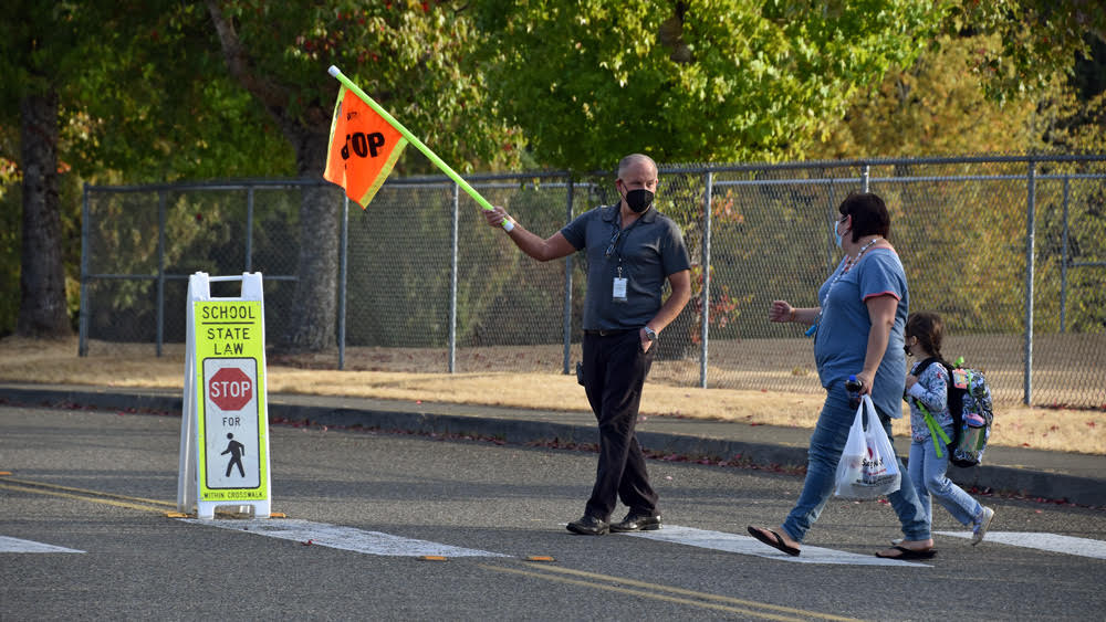 Crossing guard holds out orange STOP flag in crosswalk while parent and child walk across crosswalk.